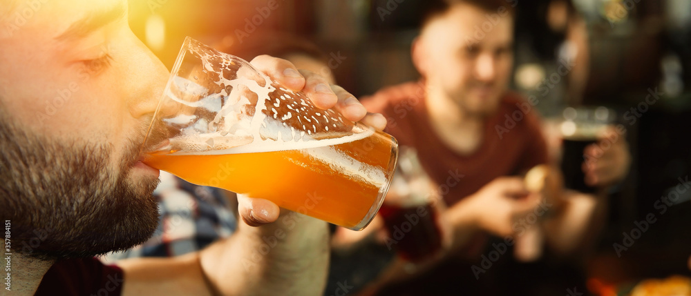 Fototapeta Young man drinking tasty beer in pub, space for text. Banner design