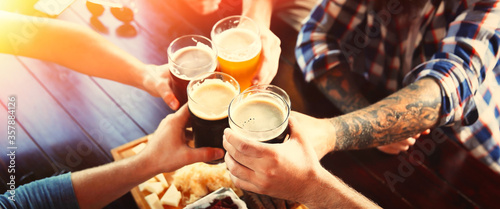 Fotografia Group of friends toasting with beer in pub, closeup