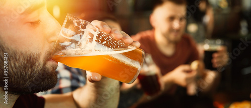 Fototapeta Young man drinking tasty beer in pub, space for text. Banner design obraz