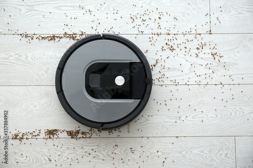 Stampa su Tela Modern robotic vacuum cleaner removing scattered buckwheat from wooden floor, to