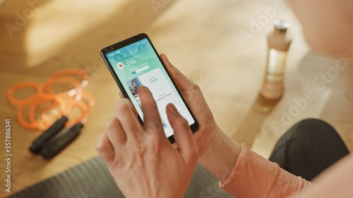 Fotomural Over Shoulder Shot: Fit Woman Holds Smartphone, Uses Fitness Tracking App, Uses Gesture to Choose Premium Workout Videos