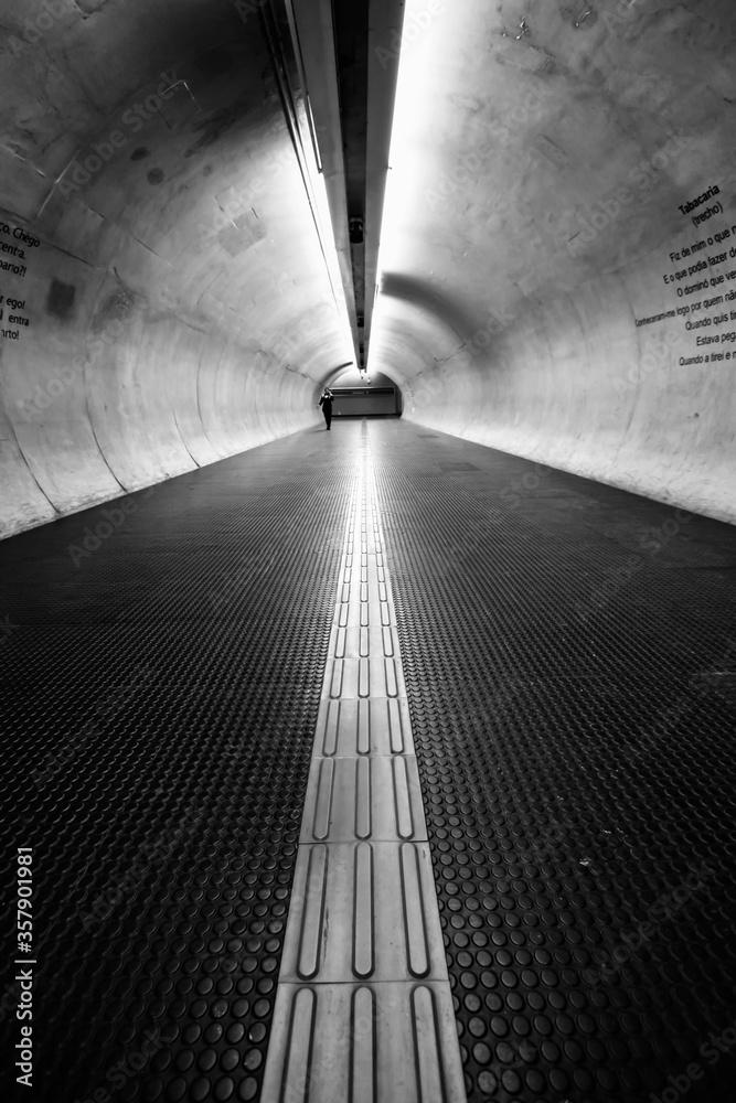Fototapeta Túnel do metrô de São Paulo, em grande angular. Perspectiva com apenas uma pessoa isolada distante.