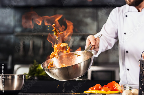 Fototapeta Chef hands keep wok with fire. Closeup chef hands cook food with fire. obraz