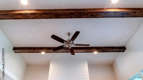 Photo Panorama crop Ceiling fan with lights between decorative wood beams inside livin