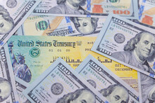 Stack Of 100 Dollar Bills With Coronavirus Stimulus Payment Check To Show The Virus Payment To Americans. Concept IRS Tax Refund Or Coronavirus Stimulus Payments. Global Pandemic Covid 19 Lock Down