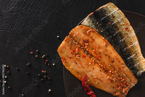 Smoked marinated mackerel fillets or fillet herring fish with spices, greens and slice of bread on plate over dark stone background. Mediterranean food, appetizer, seafood, top view