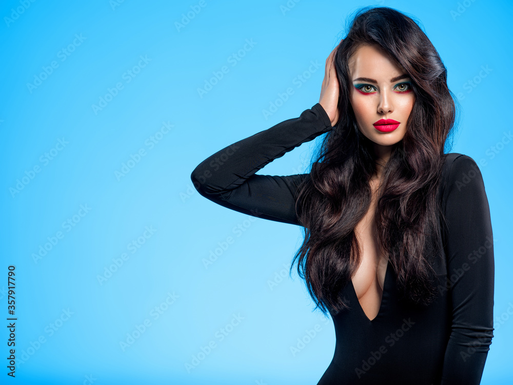 Fototapeta Portrait of beautiful young woman with bright blue makeup.  Pretty girl with long black hair. Brunette woman in a black clothes. Sexy girl. Beautiful brunette with bright red lipstick on her lips..