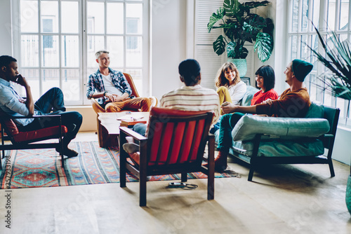 Fotografiet Group of delighted multiethnic friends chatting at home