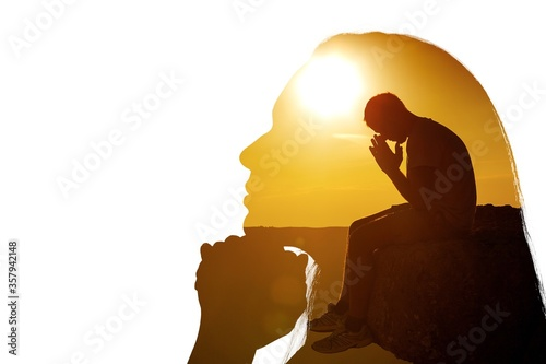 Photo Young man pray outdoor on top of mountains in the sunset