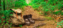 Hiking Nature Background - Close Up From Rustic Leather Hiking Boots And Hiking Backpack On Ground In The Forest