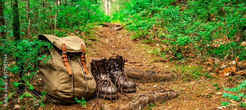 Fotografiet Hiking nature background - Close up from rustic leather hiking boots and hiking