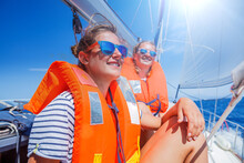 Two Young Beautiful Girls On Board Of Sailing Yacht On Summer Cruise In Greece. Travel Adventure, Yachting On Family Vacation.