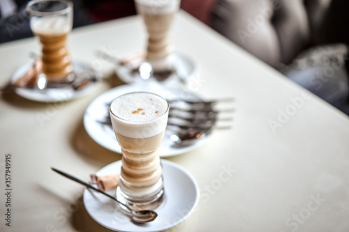 Fotografie, Obraz Latte glass with layered latte, cappuccino or mocha with foam on table in cafe with milk saucer and spoon