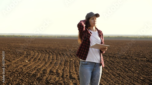 Fototapeta business woman checks her box. farmer woman with tablet in the field. female agronomist checks the quality of sowing grain. A farmer checks the quality of the soil before sowing. obraz