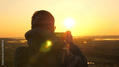 traveler takes photos and videos on his smartphone at dawn, from the mountain in rays of the beautiful sun Canvas Print