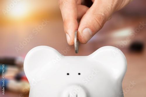 Saving money concept, human hand put money in a piggy bank Fototapeta