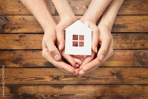 Fototapeta Hands holding house model on wooden background obraz