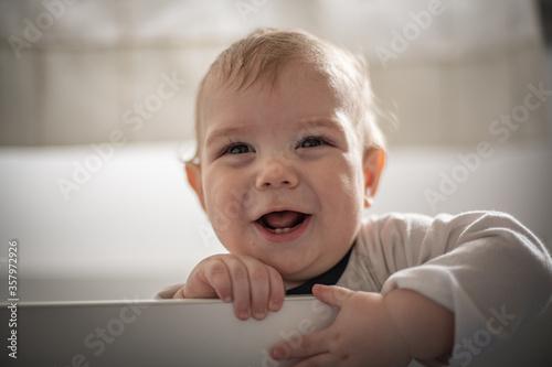Leinwand Poster Bebé varón rubio parado en su cuna riendo y mirando hacia su derecha