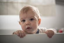 Bebé Varón Rubio Parado En Su Cuna  Mirando Hacia Su Derecha