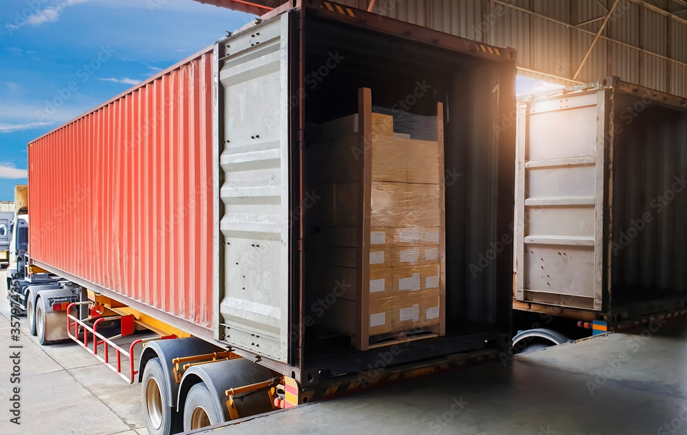 Fototapeta Road freight industry logistics and transportation. Warehouse dock cargo load shipment into shipping container truck. Stack shipment boxes on pallet inside a truck.