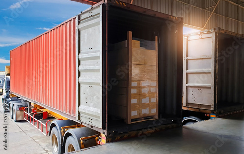 Fototapeta Road freight industry logistics and transportation. Warehouse dock cargo load shipment into shipping container truck. Stack shipment boxes on pallet inside a truck. obraz