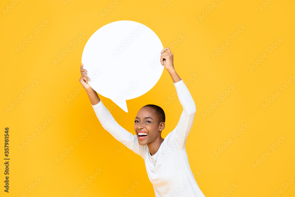 Fototapeta Cheerful happy young African American woman smiling and holding speech bubble with empty space for text overhead isolated on yellow background