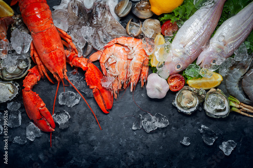 Obraz na plátně Shellfish and crustacean seafood with selection of fresh lobster, shrimp, fish, oyster, squid and crab on dark rustic background