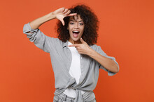 Excited Young African American Woman Girl In Gray Casual Clothes Isolated On Orange Background Studio Portrait. People Emotions Lifestyle Concept. Mock Up Copy Space. Making Hands Photo Frame Gesture.
