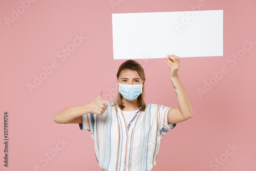 Fototapeta Young girl in casual striped shirt sterile face mask isolated on pink background. Epidemic pandemic coronavirus 2019-ncov sars covid-19 flu virus concept. Hold board with place text showing thumb up. obraz