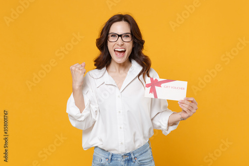 Happy young brunette business woman in white shirt glasses isolated on yellow background Fototapet