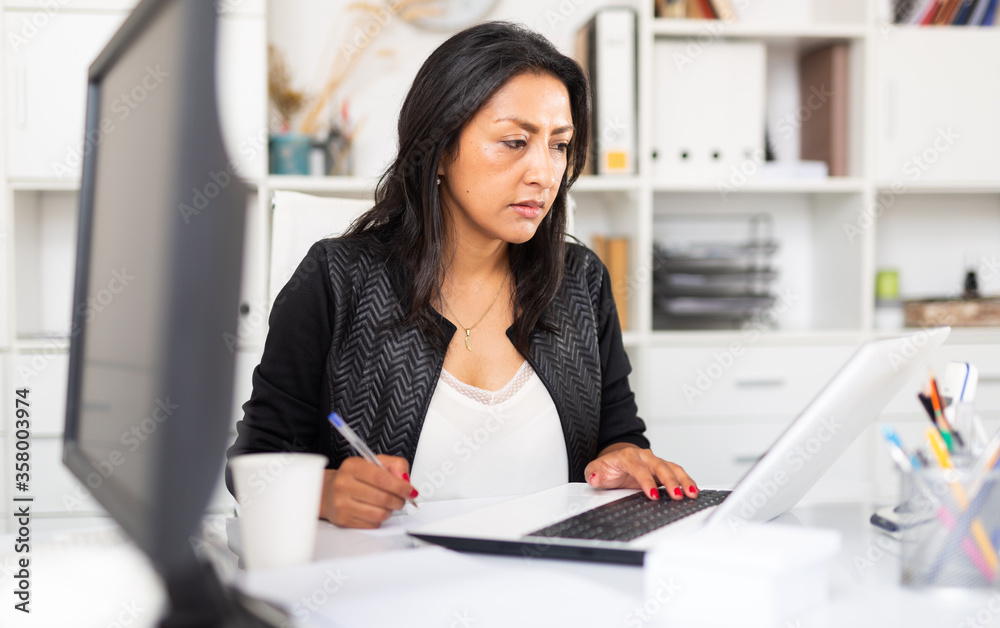 Fototapeta Busy female entrepreneur in office with papers and laptop