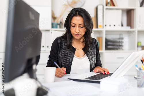 Leinwand Poster Busy female entrepreneur in office with papers and laptop
