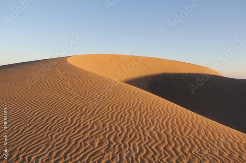 Amazing shot of a desert dune on blue sky background