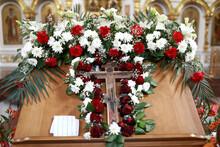 Flowers Around Wooden Cross In Church
