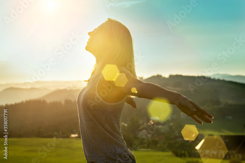 Obraz Happy woman with open arms stay on the peak of the mountain cliff edge under sunset light sky enjoying the success, freedom and bright future.  - fototapety do salonu