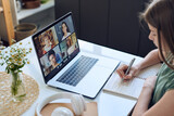 Close-up of concentrated teenage girl sitting at table and making notes while using video conferencing platform for online education