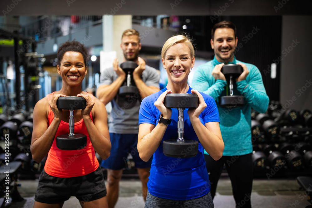 Fototapeta Group of sportive people in gym. Happy fit friends workout, exercise in fitness club