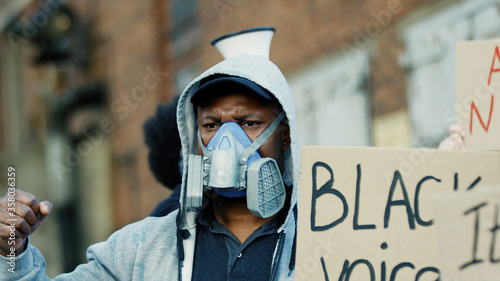 Multiethnic young male protesters in masks and respirators protesting against racism and police illegal acts Wallpaper Mural
