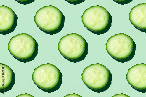 Obraz Regular seamless pattern of cucumber slices on a  pastel mint background.Photo collage,hard light, shadow,pop art design. Food blog, vegetable background. Printing on fabric, wrapping paper.Top view. - fototapety do salonu