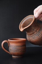 Clay Cup And Tilted Clay Jug In A Man's Hand On A Black Background