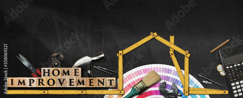 Fotografiet Wooden folding ruler in the shape of house on a blackboard with work tools, text