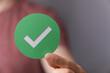 Leinwandbild Motiv hand holding green checkmark