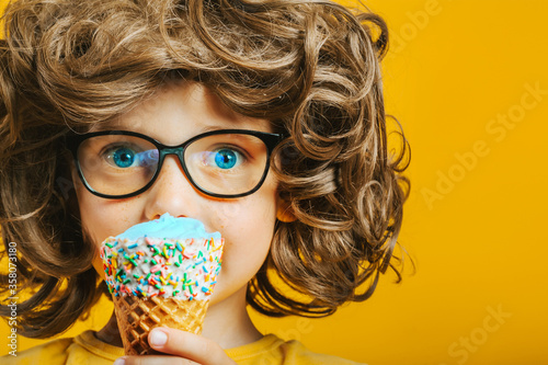 boy with long hair happily eats ice cream #358073180