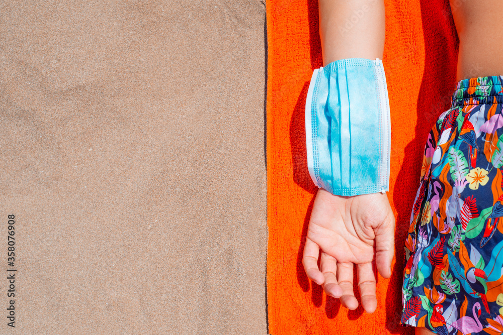 Fototapeta man wearing a surgical mask in his arm on the beach