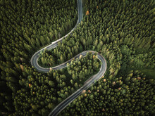 Aerial View Of Countryside Road Passing Through The Green Forest And Mountain