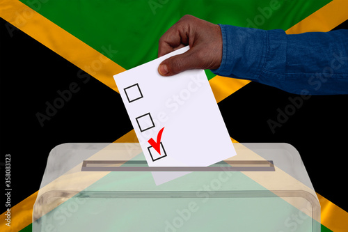 male voter drops a ballot in a transparent ballot box on the background of the n Canvas-taulu