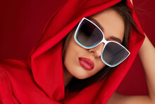 Portrait Of Beautiful Brunette Sexy Girl With Luxurious Make-up In White Sunglasses And Red Headscarf On Red Background