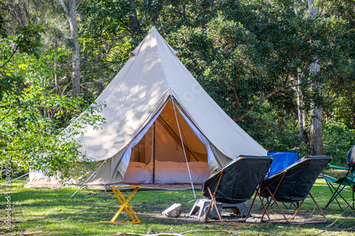 Fotomural Glamping camping teepee tent and chairs at the campsite