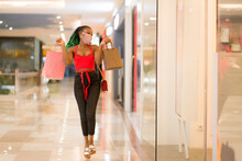 Young African American Woman At Shopping Mall In New Normal After Covid-19 - Happy And Beautiful Black Girl In Face Mask Holding Shopping Bags Enjoying At Beauty Fashion Store