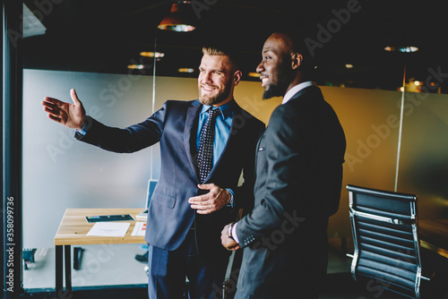 Fotografia Cheerful caucasian male broker showing office interior African American entrepreneur dressed in formal wear during friendly meeting